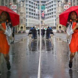 Una mujer camina en la City de Londres durante un día de lluvia. | Foto:Tolga Akmen / AFP