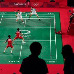 Miembros de los medios de comunicación son fotografiados en la arena mientras el indonesio Marcus Fernaldi Gideon y el indonesio Kevin Sanjaya Sukamuljo juegan en su partido de la fase de grupos de bádminton masculino de dobles contra el taiwanés Wang Chi-lin y el taiwanés Lee Yang durante los Juegos Olímpicos de Tokio 2020. | Foto:Pedro Pardo / AFP