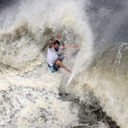 El brasileño Italo Ferreira compite durante la final de la medalla de oro de surf masculino en la playa de Tsurigasaki, en Chiba, durante los Juegos Olímpicos de Tokio 2020. | Foto:Yuki Iwamura / AFP
