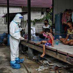 Un voluntario de la organización Zendai habla con una familia en aislamiento domiciliario en una comunidad afectada por el virus Covid-19 en el distrito de Nong Chok, en las afueras de Bangkok, mientras las camas de hospital para los pacientes infectados siguen escaseando en todo el país. | Foto:Lillian Suwanrumpha / AFP