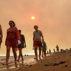 Turistas caminan durante un incendio forestal masivo en una una región turística del Mediterráneo en la costa sur de Turquía, cerca de la ciudad de Manavgat. Al menos tres personas murieron y más de 100 resultaron heridas mientras los bomberos luchaban contra las llamas que envolvían una región turística del Mediterráneo en la costa sur de Turquía. | Foto:Ilyas Akengin / AFP
