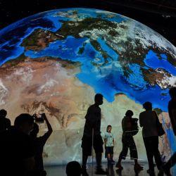 Una representación de nuestro planeta Tierra se ve mientras la gente visita el recién inaugurado Planetario de Shanghai. | Foto:Hector Retamal / AFP