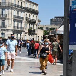 Unas personas caminan junto a una pancarta que indica que es obligatorio llevar mascarilla en la ciudad en la plaza de la Comedie, en el centro de Montpellier, sur de Francia, mientras la cuarta ola de Covid-19 golpea a Francia. | Foto:Pascal Guyot / AFP