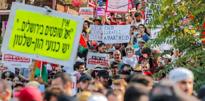 Activistas palestinos, israelíes y extranjeros levantan pancartas y carteles durante una manifestación contra la ocupación israelí y la actividad de los asentamientos en los territorios palestinos y en el este de Jerusalén, en el barrio palestino de Sheikh Jarrah.