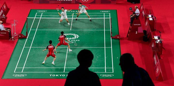 Miembros de los medios de comunicación son fotografiados en la arena mientras el indonesio Marcus Fernaldi Gideon y el indonesio Kevin Sanjaya Sukamuljo juegan en su partido de la fase de grupos de bádminton masculino de dobles contra el taiwanés Wang Chi-lin y el taiwanés Lee Yang durante los Juegos Olímpicos de Tokio 2020.