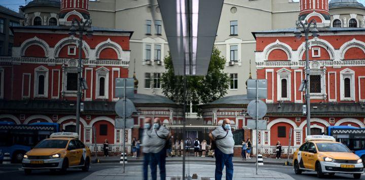 Un hombre con una máscara facial en medio de la actual pandemia de Covid-19 se refleja en una entrada del metro en el centro de Moscú.