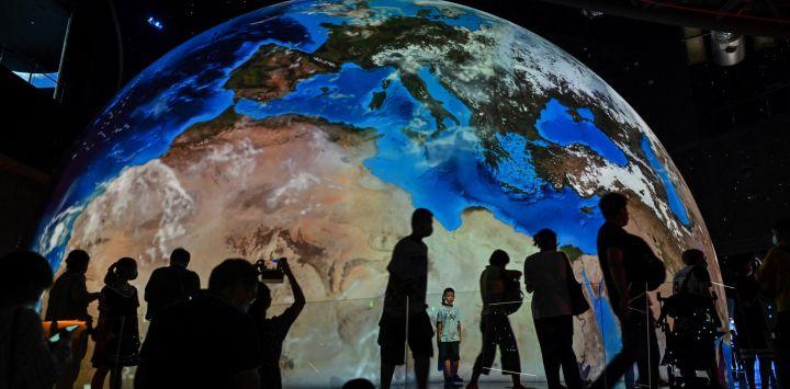 Una representación de nuestro planeta Tierra se ve mientras la gente visita el recién inaugurado Planetario de Shanghai.