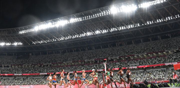 Una vista general muestra a los atletas que compiten en un estadio emtpy en las series de 5.000 metros femeninos durante los Juegos Olímpicos de Tokio 2020 en el Estadio Olímpico de Tokio.