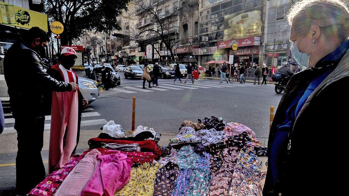 A street vendor sells clothes alongside Avenida Corrientes in the Balvanera neighbourhood, on Thursday, July 22, 2021.