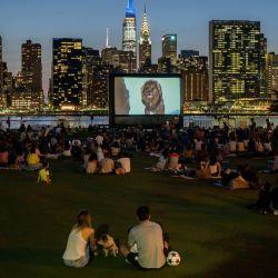 La gente se sienta en un parque público mientras ve una proyección al aire libre del Rey León ante el horizonte de Manhattan en la ciudad de Long Island, Nueva York.   Foto:Ed Jones / AFP