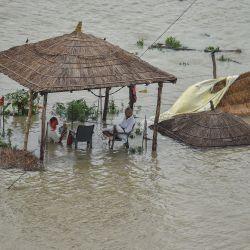 Unas personas se sientan bajo una cabaña de paja sumergida después de que el aumento del nivel de las aguas del río Ganges inundara la zona cercana a las orillas del río, en Allahabad.   Foto:Sanjay Kanojia / AFP