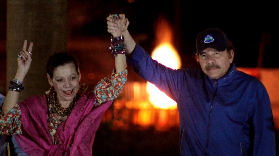 In this file photo taken on March 21, 2019 Nicaragua's President Daniel Ortega (right) and his wife, Vice-President Rosario Murillo, gesture at the crowd during the inauguration of the Nejapa flyover in Managua.
