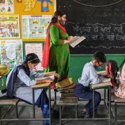 Alumnos asisten a su clase dentro de una escuela después de que las autoridades relajaran las normas de cierre y reabrieran las instituciones educativas en Amritsar.   Foto:Narinder Nanu / AFP