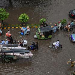 Los transeúntes se abren paso a través de una calle inundada tras las fuertes lluvias monzónicas en Lahore.   Foto:Arif Ali / AFP