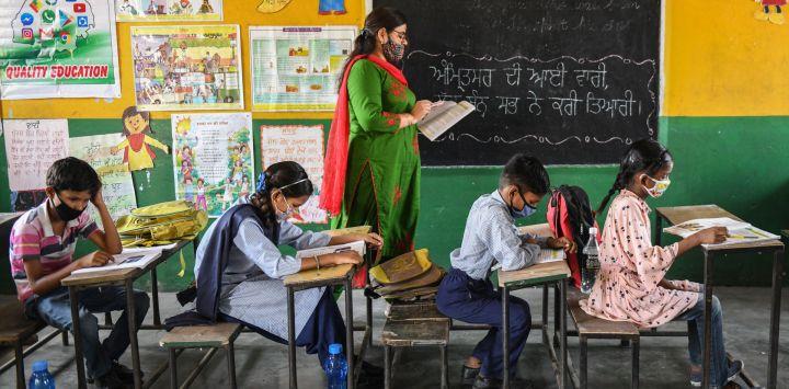 Alumnos asisten a su clase dentro de una escuela después de que las autoridades relajaran las normas de cierre y reabrieran las instituciones educativas en Amritsar.