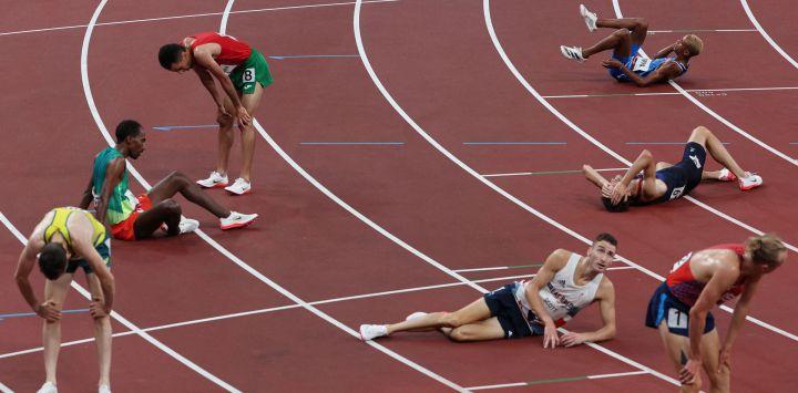 Los atletas reaccionan después de competir en las series de 5.000 metros masculinos durante los Juegos Olímpicos de Tokio 2020 en el Estadio Olímpico de Tokio.