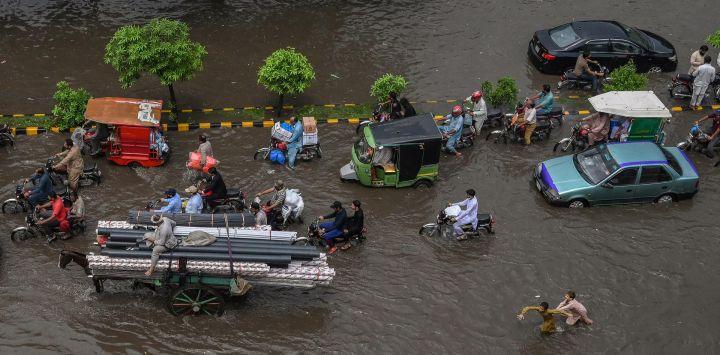 Los transeúntes se abren paso a través de una calle inundada tras las fuertes lluvias monzónicas en Lahore.