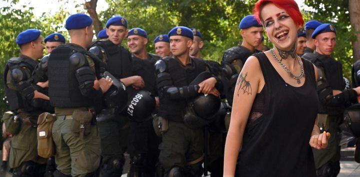 Un activista sonríe ante la mirada de los agentes de policía durante la protesta