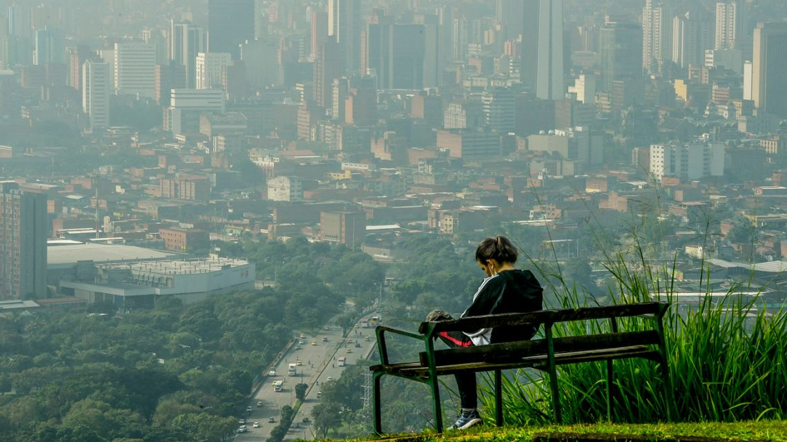 A woman wacthes the view from the Volador hill in Medellín, Colombia, on June 12, 2021. The city has been awarded and recognized for its urban planning of green corridors and is known for its eco-friendly habitat.