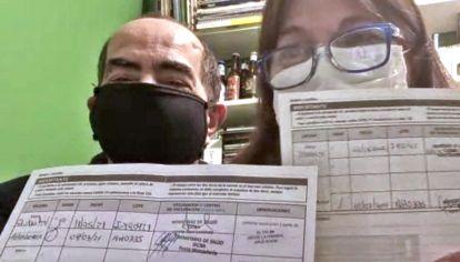 Voluntarios de las pruebas de combinación de vacunas covid con su carnet.