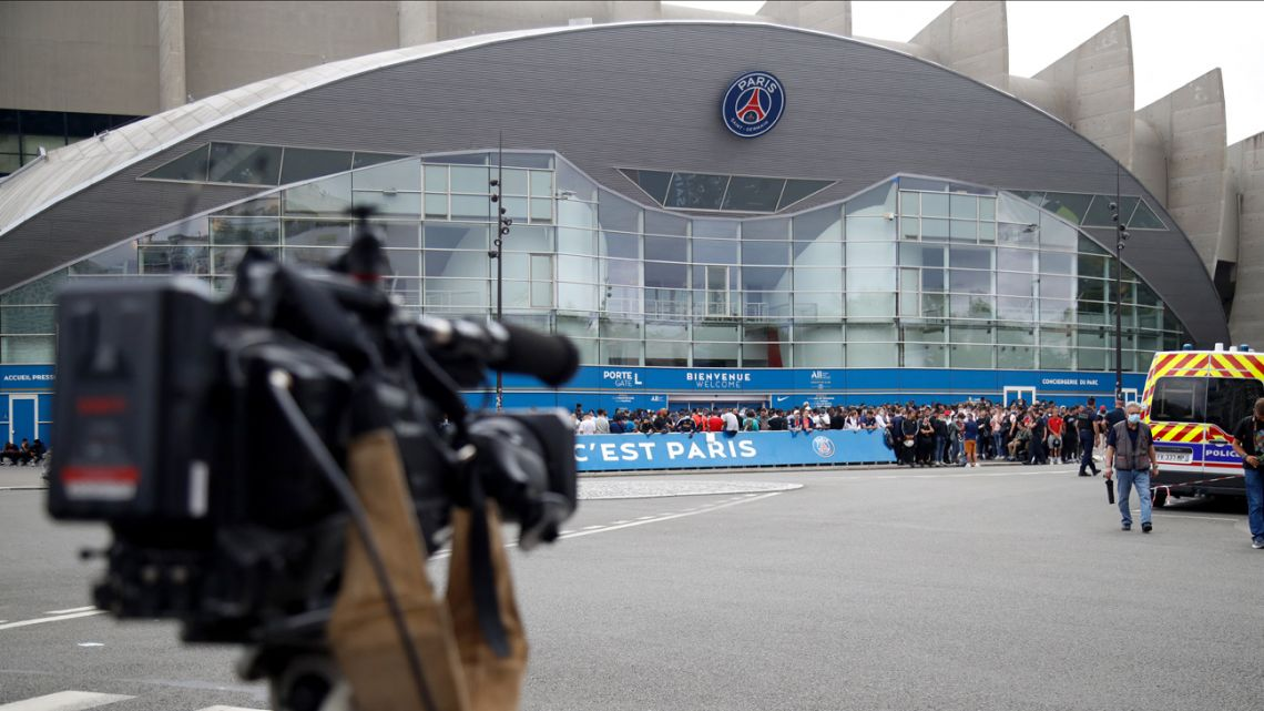 A news reporter camera focuses at people gathering outside the Parc des Princes stadium in Paris, ahead of Leo Messi's reported transfer to Paris Saint Germain.