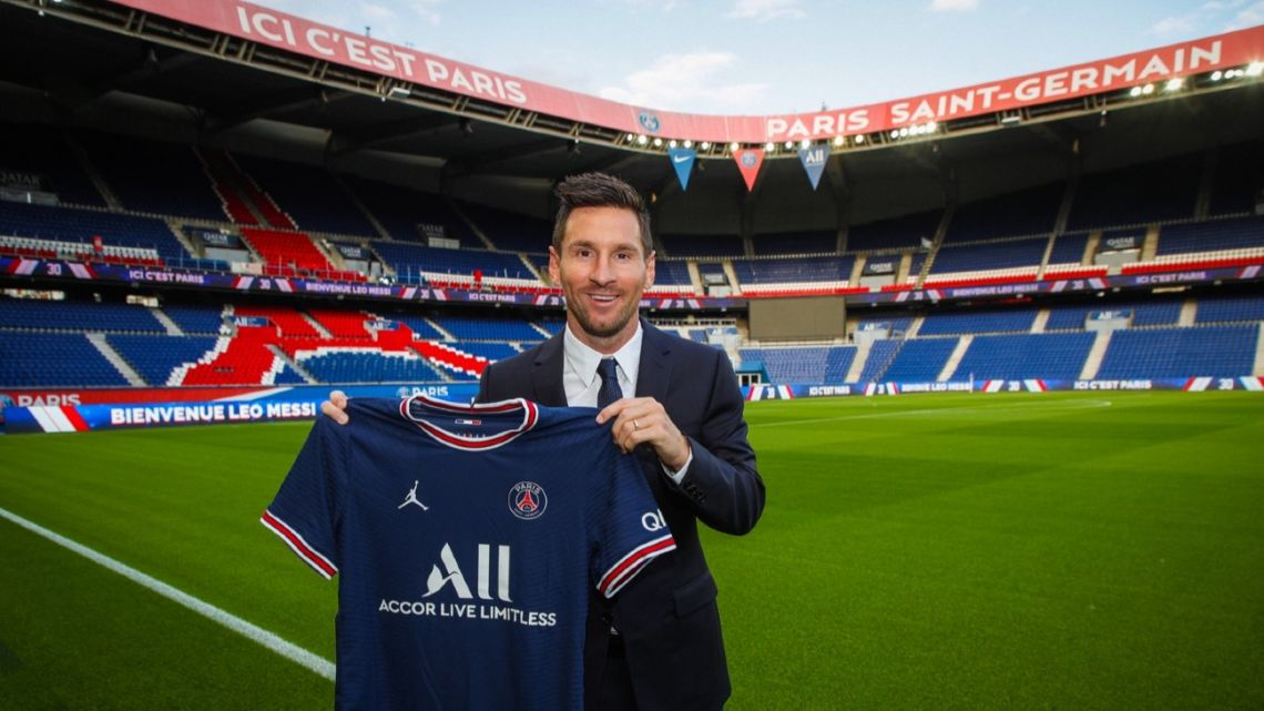 Lionel Messi holds up a Paris St Germain shirt at the Parc des Princes stadium after signing for the French side.