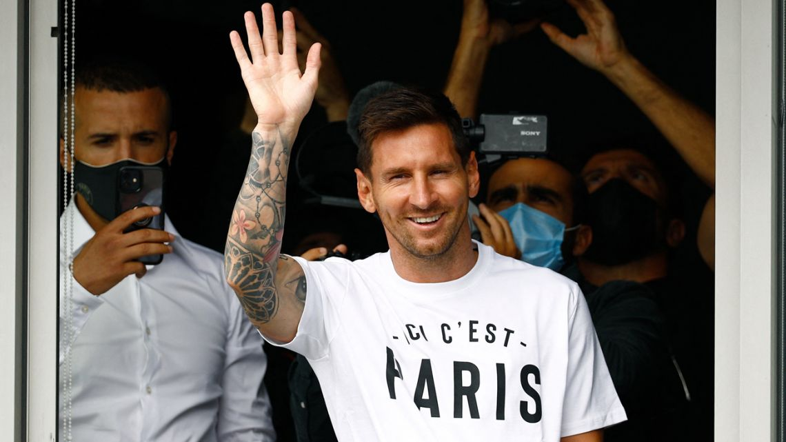 """Lionel Messi salutes supporters from a window after he landed on August 10, 2021 at Le Bourget airport, north of Paris, to become Paris Saint-Germain's new player following his departure from Barcelona, the club he has represented for the entirety of his 17-year professional career so far. Asked by reporters at Barcelona's El Prat airport if the Argentine star would later on sign with the French club, Jorge Messi, the father and player's agent, said: """"Yes""""."""