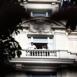 Two hands from a fan form a heart encircling Lionel Messi in the distance, as he looks at fans from a balcony of the Royal Monceau hotel in Paris on August 10, 2021.