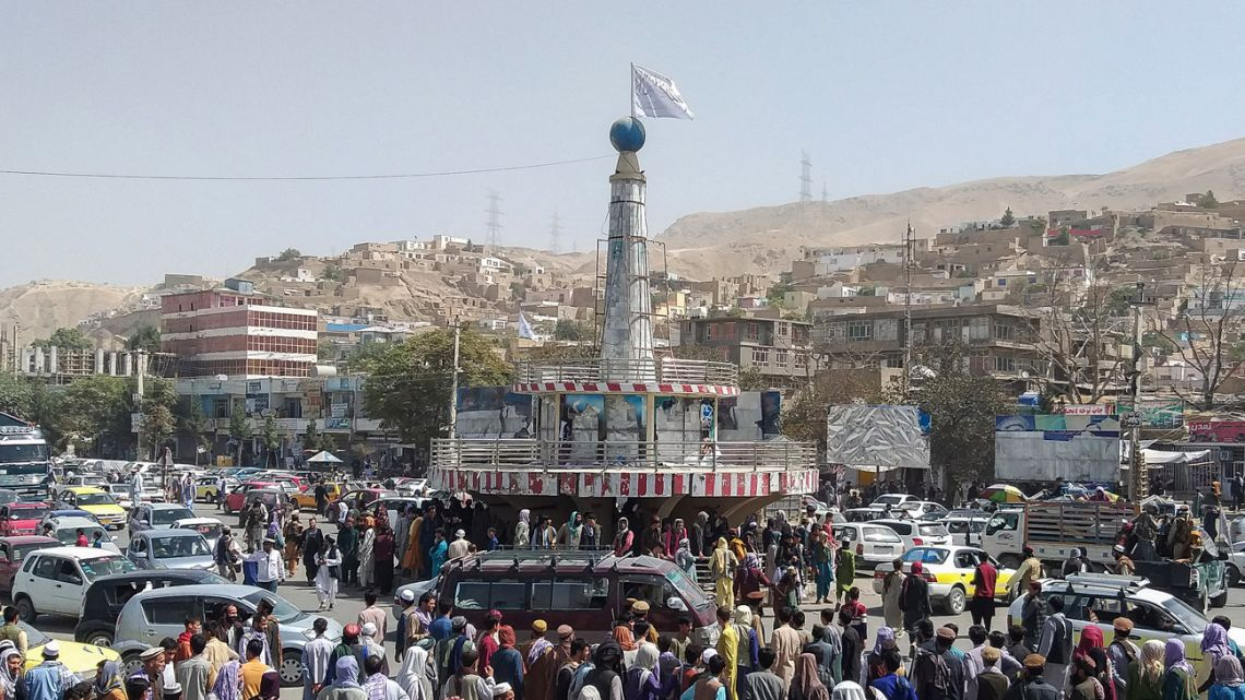 A Taliban flag is seen on a plinth with people gathered around the main city square at Pul-e-Khumri on August 11, 2021 after Taliban captured Pul-e-Khumri, the capital of Baghlan province about 200 kms north of Kabul.
