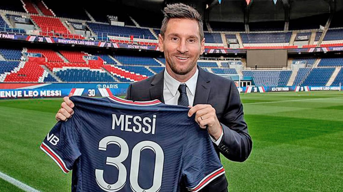 Lionel Messi poses with a PSG shirt on the pitch at the Parc des Princes.