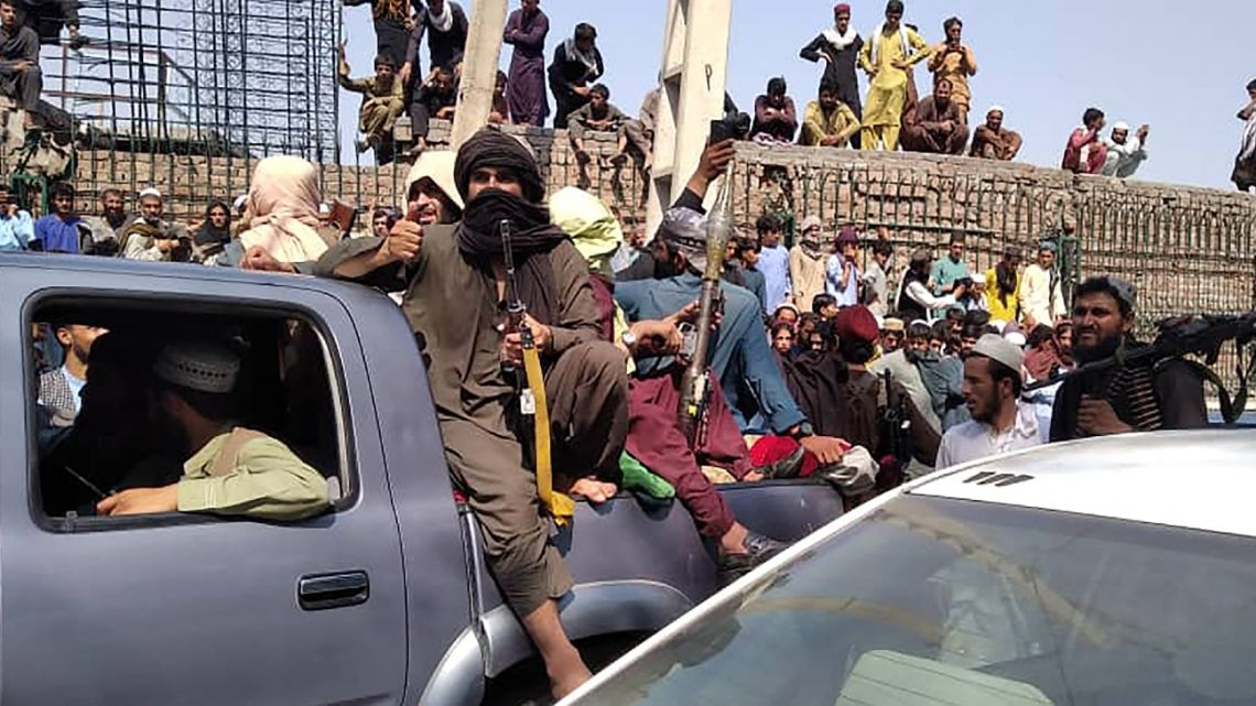Taliban fighters sit on a vehicle along the street in Jalalabad province on August 15, 2021.