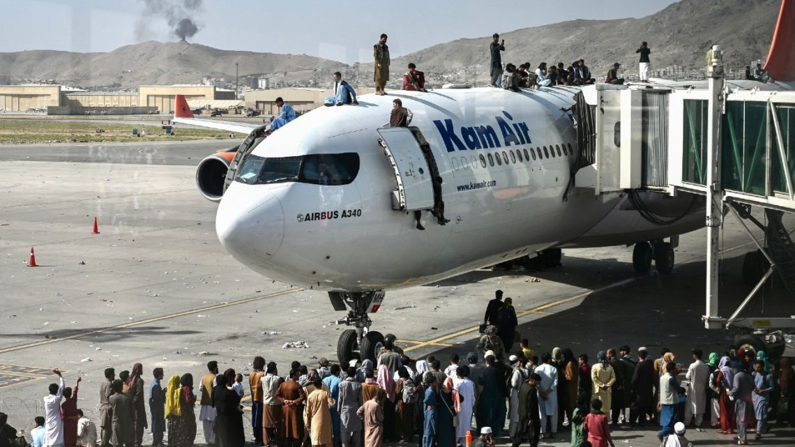 Afghan people climb atop a plane as they wait at the Kabul airport in Kabul on August 16, 2021, after a stunningly swift end to Afghanistan's 20-year war, as thousands of people mobbed the city's airport trying to flee the group's feared hardline brand of Islamist rule.