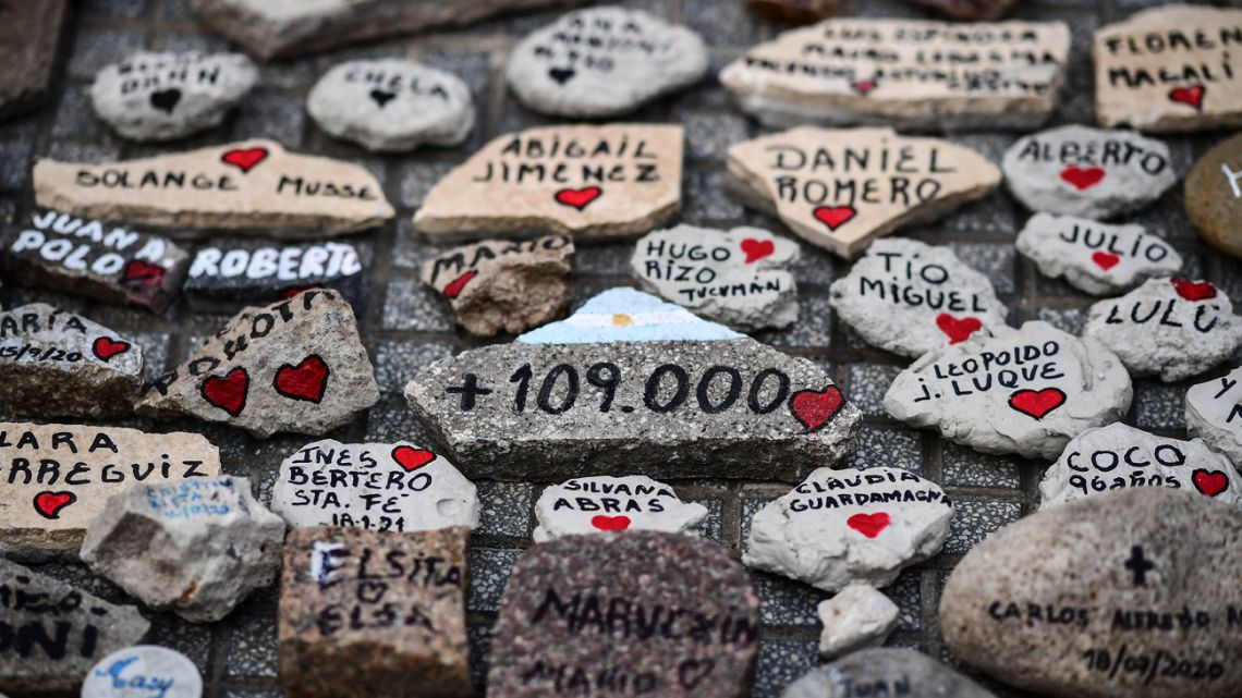 """View of stones with names outside the Casa Rosada government house during the """"march of the stones"""" in homage to COVID-19 victims, in Buenos Aires, on August 16, 2021."""