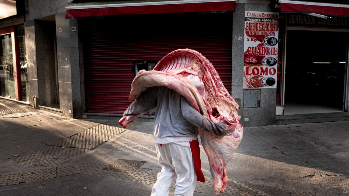 A butcher takes delivery of a beef carcass.