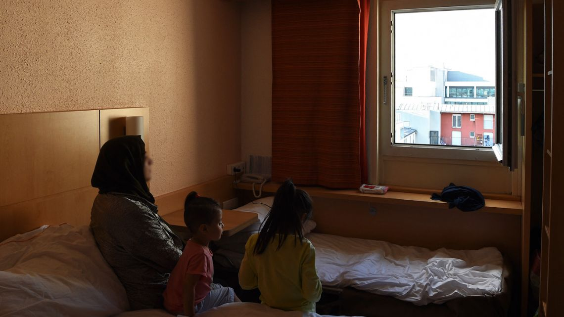 An Afghan refugee, Maryam, and her children sit in an hotel room in Paris on August 22, 2021, after being evacuated from Kabul with the help of the French authorities. The military operation dubbed