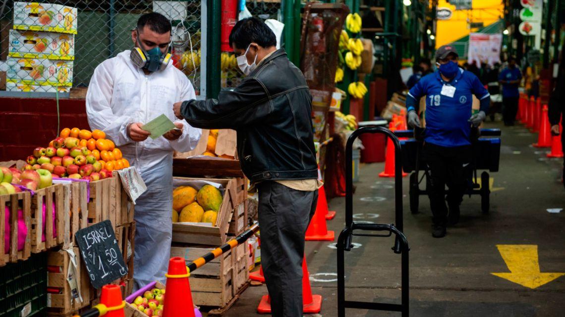 A shopper checks prices with a vendor at a marketplace in Lima, Peru.