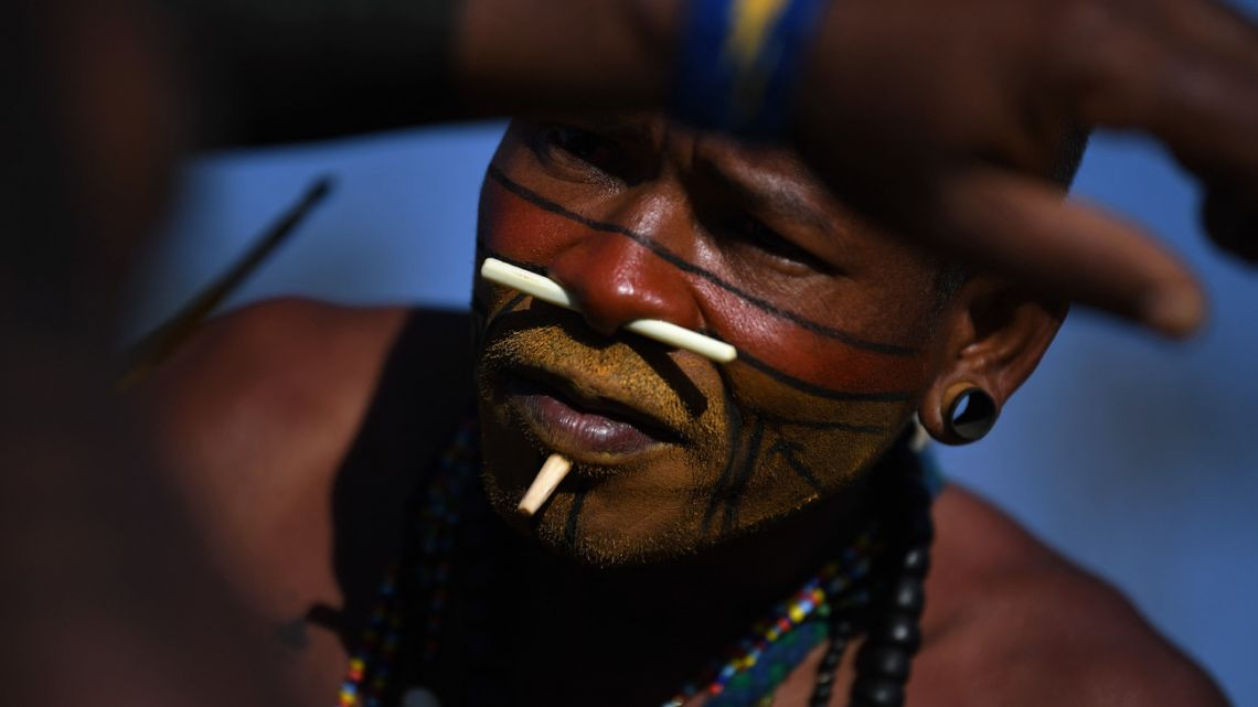An indigenous man from the Pataxo tribe paints the body of a colleague at a protest camp in Brasilia, Brazil on August 25, 2021. Thousands of indigenous protesters gathered in the Brazilian capital bearing bows and arrows and traditional headdresses as the Supreme Court prepared to take up a case Wednesday that could eliminate reservations on their ancestral lands.