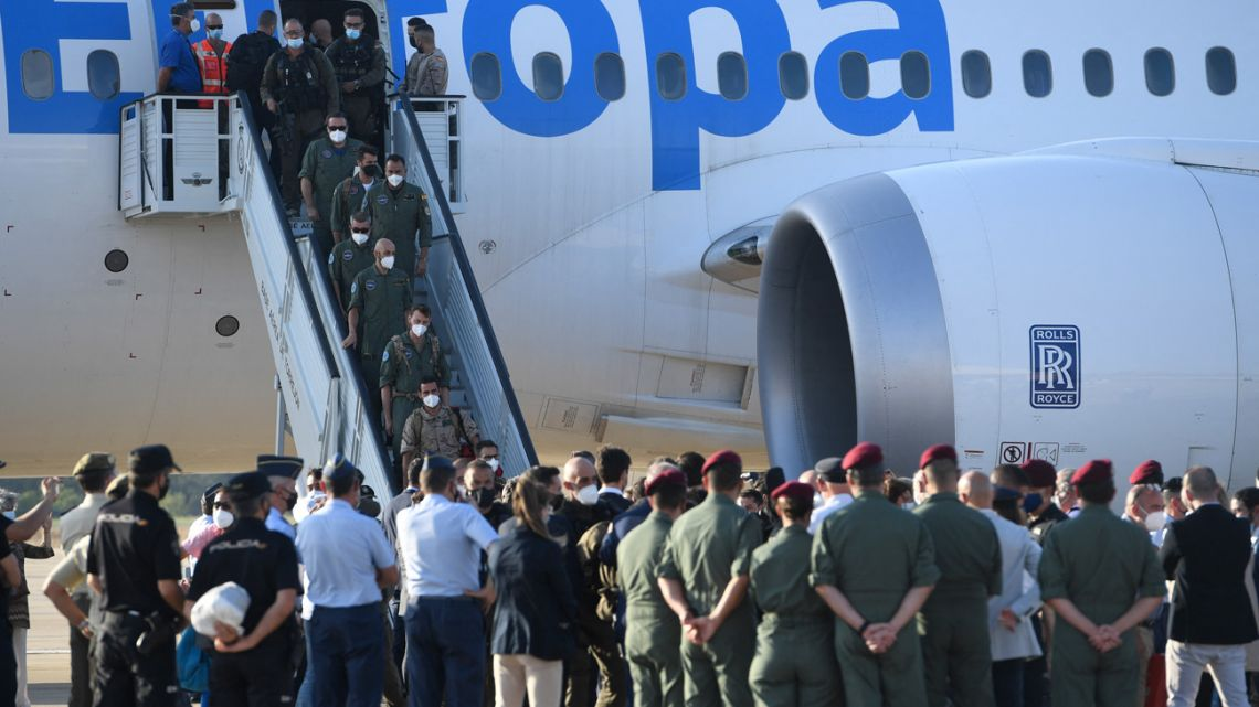 Members of Spanish National Police forces and military personnel who were stationed in Afghanistan disembark from one of the last two Spanish evacuation flights, at the Torrejon de Ardoz air base, 30 km from Madrid, on August 27, 2021. Spain announced the end of its Kabul evacuations today after a nine-day operation that saw more than 2,200 people flown out of the strife-torn country following the Taliban takeover.