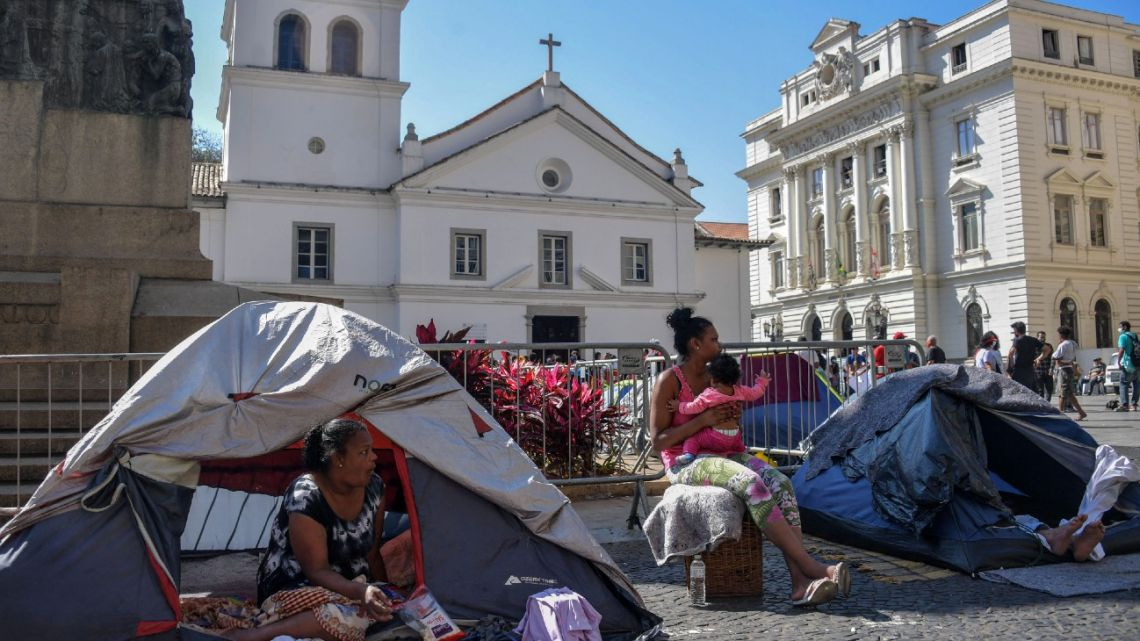 A homeless family is seen by tents at Patio do Colegio, in São Paulo downtown, Brazil, on August 19, 2021.