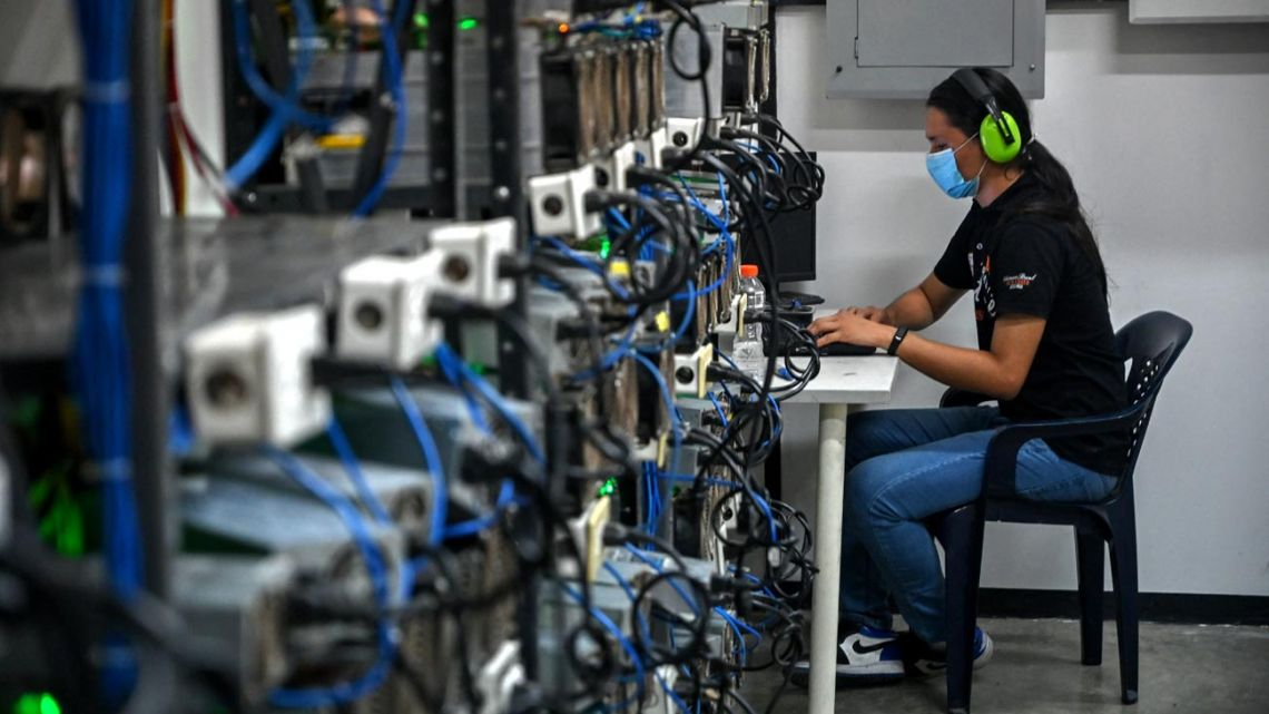 An employee inspects computers used to mine Bitcoins at the mining showroom of the Doctorminer company in Caracas on August 18, 2021.