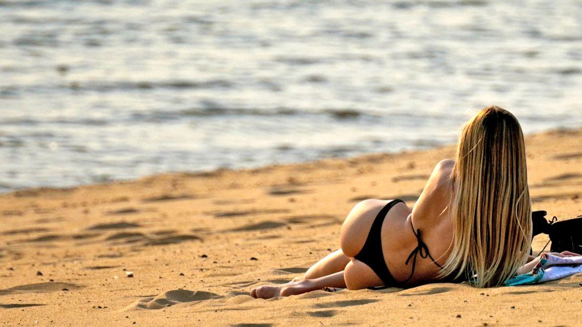 A woman sunbathes next to the Paraná River.