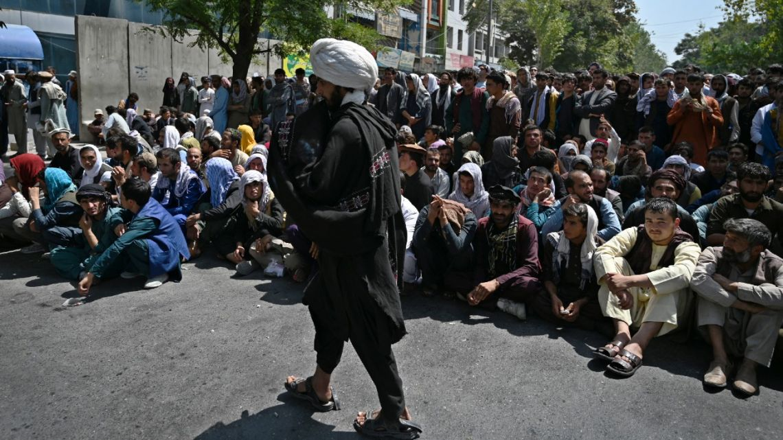 A Taliban fighter walks in front of people sitting along a road outside a bank waiting to withdraw money at Shar-e-Naw neighborhood in Kabul on September 4, 2021.