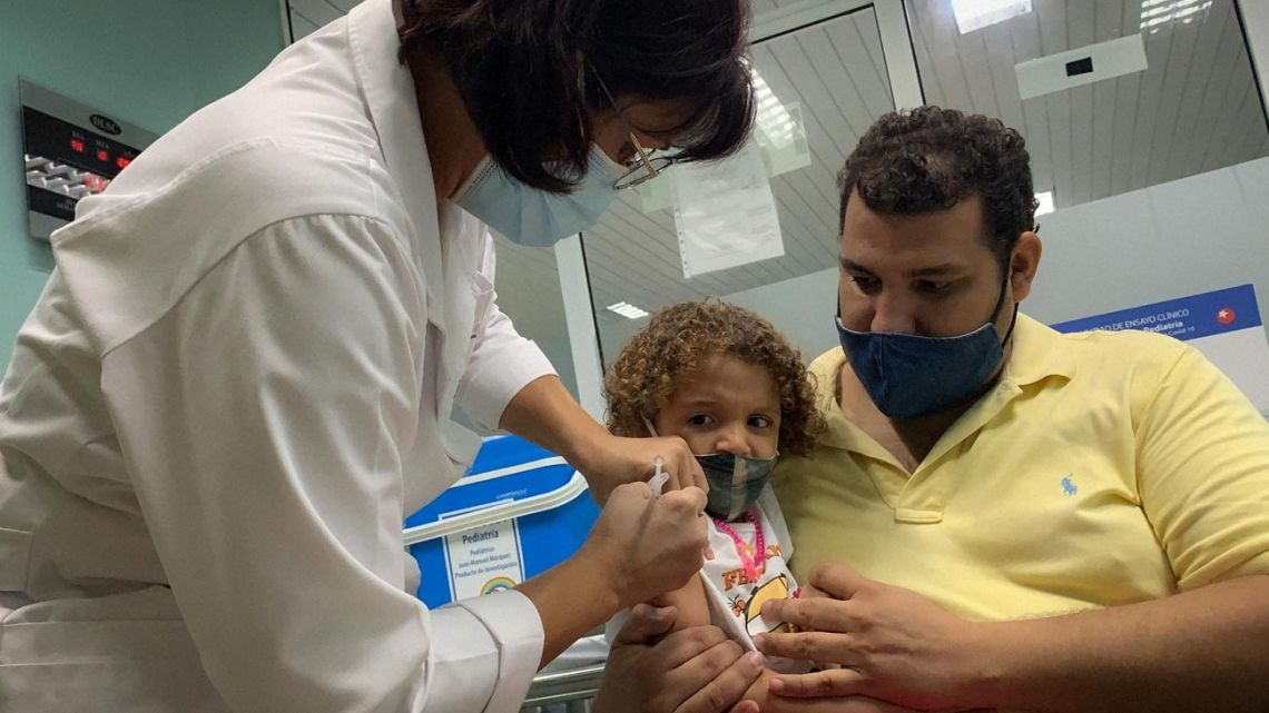 Pedro Montano holds his daughter Roxana Montano, 3, while she is being vaccinated against Covid-19 with Cuban vaccine Soberana Plus, on August 24, 2021 at Juan Manuel Marquez hospital in Havana.