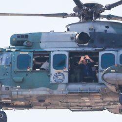 El presidente brasileño Jair Bolsonaro saluda a sus seguidores desde su helicóptero en Brasilia. | Foto:Sergio Lima / AFP