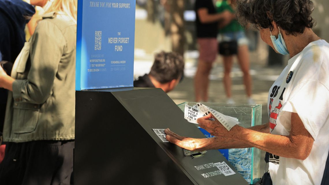 A conspiracy theorist puts stickers on a donation box at the September 11 Memorial and Museum on September 06, 2021 in New York City.