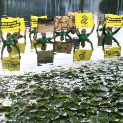 Activistas de Greenpace se sitúan en un estanque y sostienen pancartas en las que piden    Foto:Christof Stache / AFP