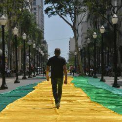 Un hombre camina junto a una carretera cubierta con la bandera brasileña durante una manifestación contra el presidente brasileño Jair Bolsonaro en Sao Paulo. | Foto:Nelson Almeida / AFP