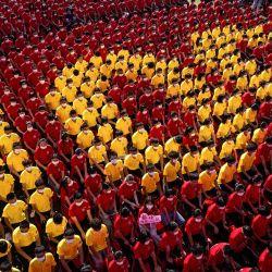 Estudiantes universitarios forman una imagen para conmemorar el centenario de la fundación del Partido Comunista de China durante una ceremonia de apertura del nuevo semestre en Wuhan, en la provincia central china de Hubei. | Foto:STR / AFP