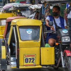 Un taxista de triciclo que lleva una máscara facial para protegerse del coronavirus Covid-19 espera a los clientes en una calle de Manila, un día antes de que las autoridades levanten la orden de permanecer en casa en medio de las infecciones récord alimentadas por la contagiosa variante Delta.   Foto:Ted Aljibe / AFP