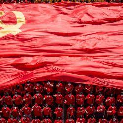 Estudiantes universitarios muestran una bandera del Partido Comunista de China para conmemorar el centenario del partido durante una ceremonia de apertura del nuevo semestre en Wuhan, en la provincia central china de Hubei.   Foto:STR / AFP